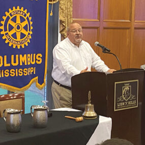 Golden Triangle LINK CEO Joe Max Higgins speaks to Rotary Club of Columbus on Tuesday as Rotarian Carey Edwards (seated) listens - Zack Plair - Dispatch Staff